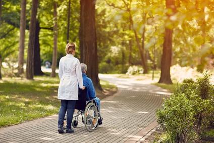 nurse helping elderly man on wheelchair outdoor.